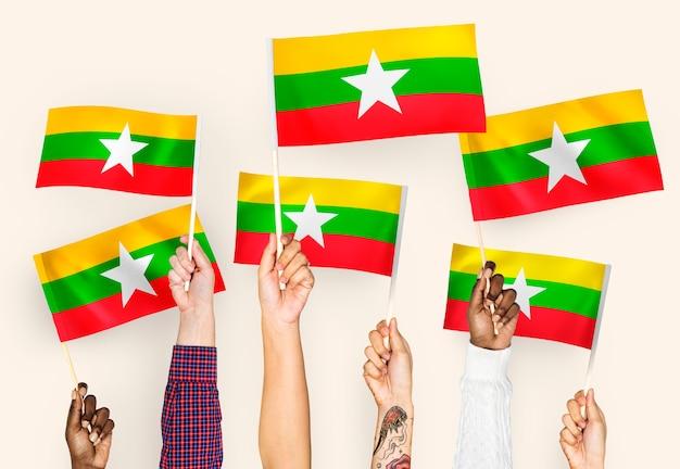 Handen met vlaggen van myanmar zwaaien
