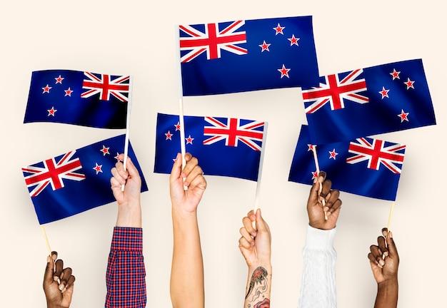 Handen met vlaggen van nieuw-zeeland zwaaien