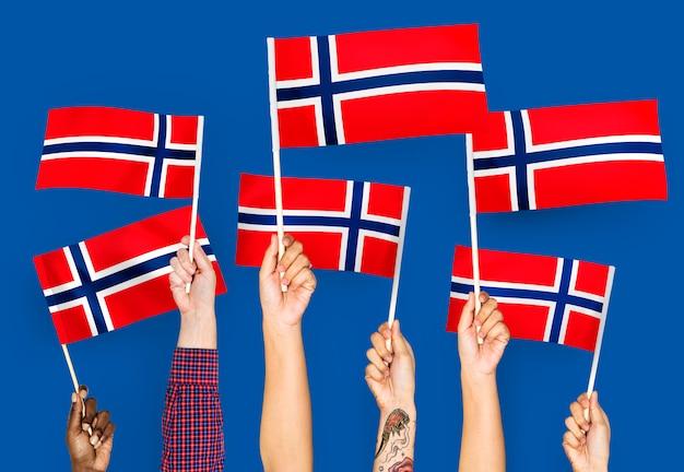 Handen met vlaggen van noorwegen zwaaien