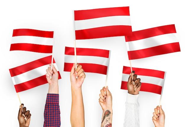 Handen met vlaggen van oostenrijk zwaaien