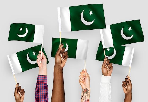 Handen met vlaggen van pakistan zwaaien