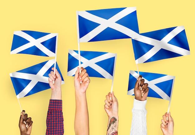 Handen met vlaggen van schotland zwaaien