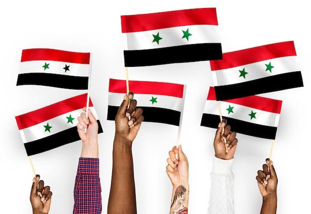 Handen met vlaggen van syrië zwaaien