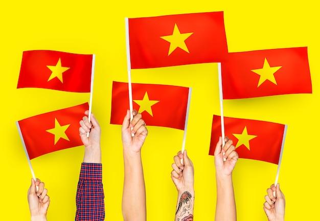 Handen met vlaggen van vietnam zwaaien