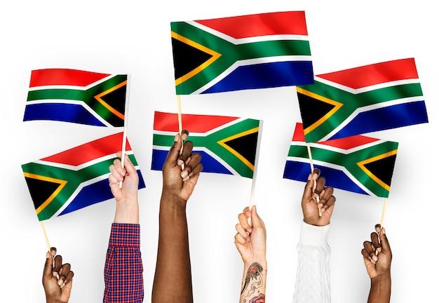 Handen met vlaggen van zuid-afrika zwaaien