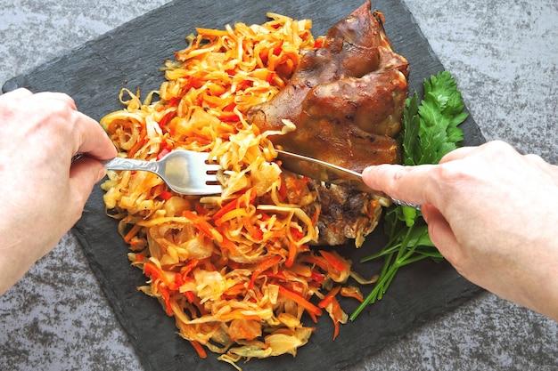 Handen met vork en mes eten gebakken varkenspoot met zuurkool. duits nationaal gerecht eisbahn