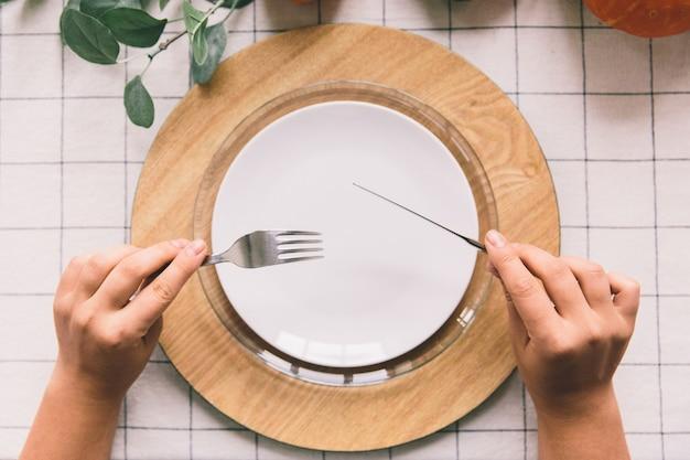 Handen met vork en mes, witte plaat op tafel.