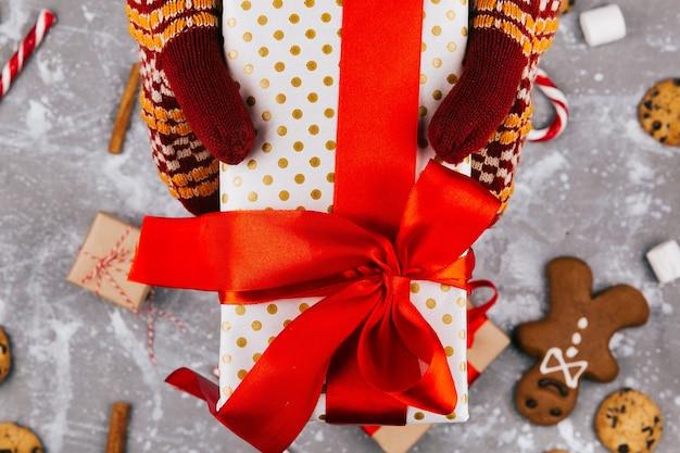 Handen met warme handschoenen houden huidige vak over kerst decor op de vloer