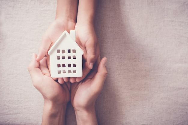 Handen met witte huis, familie thuis en dakloze onderdak concept