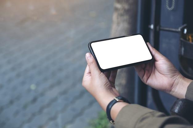 Handen met zwarte mobiele telefoon met een leeg bureaublad horizontaal
