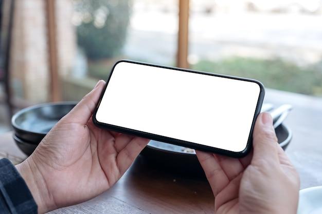 Handen met zwarte mobiele telefoon met leeg bureaublad horizontaal op de tafel