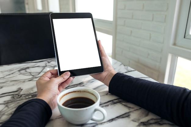 Handen met zwarte tablet pc met lege witte scherm en koffiekopje op tafel in het café