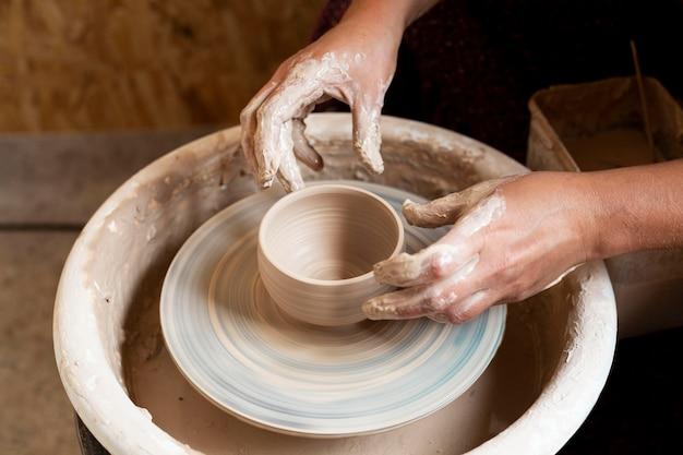 Handen modelleren in klei op een pottenbakkersschijf