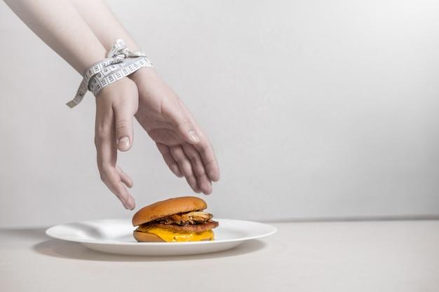 Handen nemen een hamburger, centimeter bindt handen, overtreding van het dieet, handen reiken naar een hamburger die op een bord op een witte achtergrond ligt