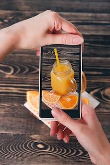 Handen nemen foto van sinaasappelen. technologie concept