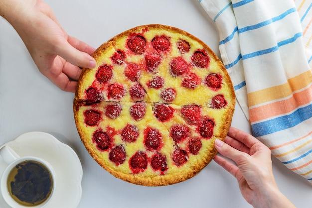 Handen nemen plakjes aardbei zelfgemaakte taart.
