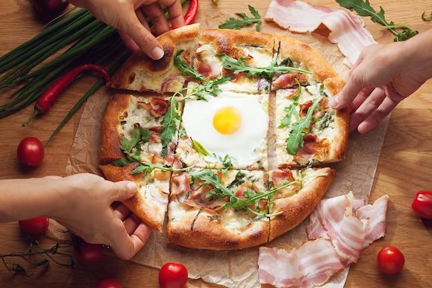 Handen nemen plakjes heerlijke pizza geserveerd op houten tafel