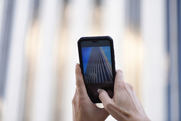 Handen nemen van een foto met een mobiele telefoon in de stad
