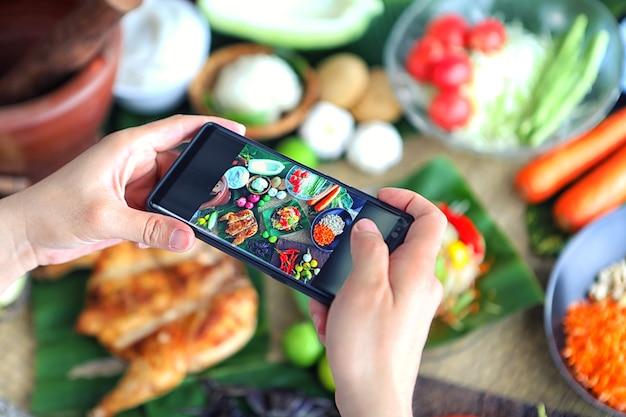 Handen nemen van foto papaja salade met smartphone