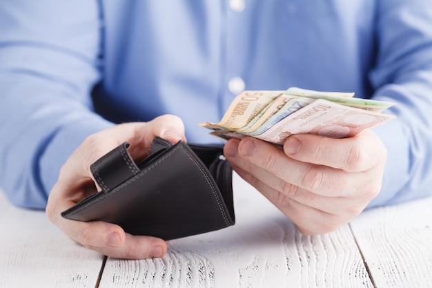 Handen nemen van geld uit portemonnee