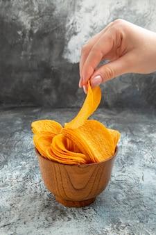 Handen nemen van zelfgemaakte heerlijke knapperige chips in een bruine kom op grijze tafel