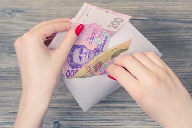 Handen oekraïense geld envelop op houten achtergrond
