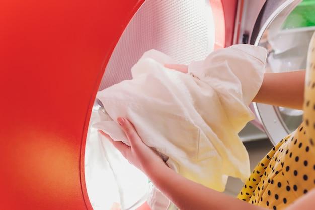 Handen om de was in de wasmachine bij de stomerij te laden.