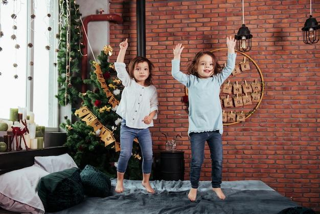 Handen omhoog. foto van de beweging. vrolijke kinderen plezier hebben en springen op het bed met decoratieve vakantie achtergrond