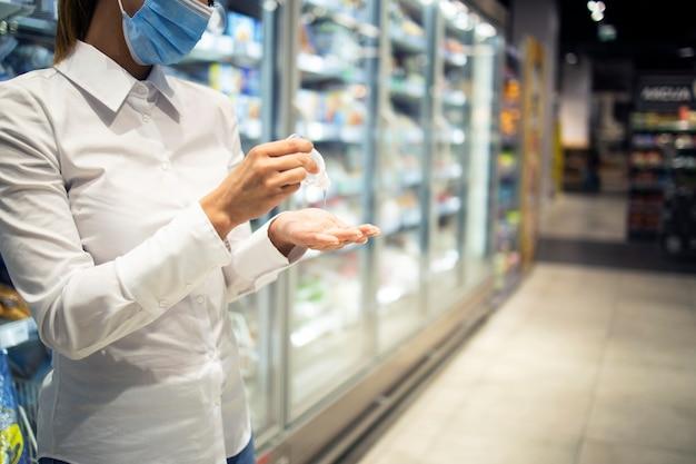 Handen ontsmetten tegen coronavirus tijdens het winkelen in de supermarkt