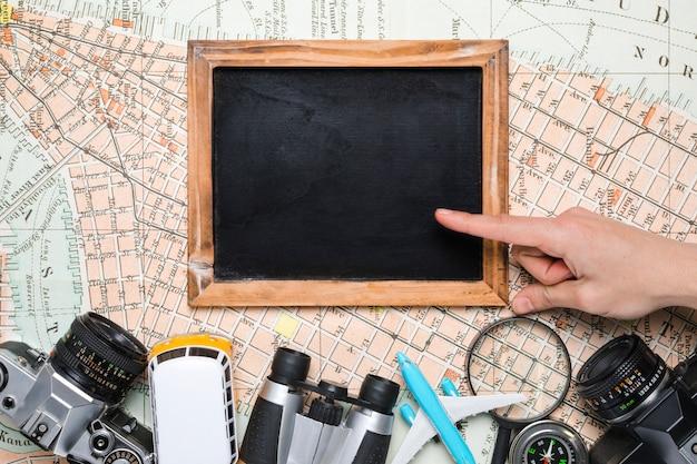 Handen op blackboard omringd door reiselementen