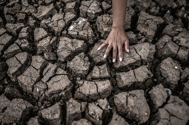Handen op droge grond, broeikaseffect en watercrisis