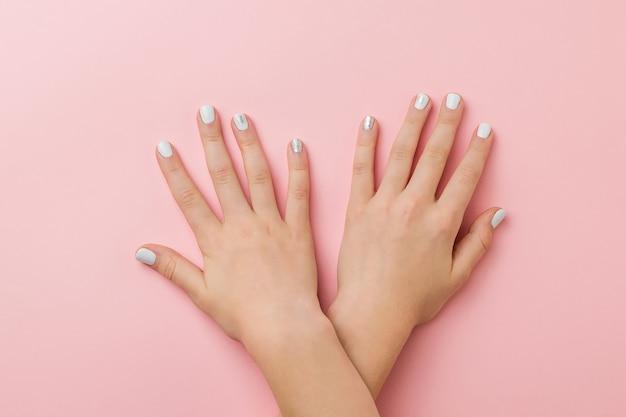 Handen op elkaar liggen met stijlvolle make-up op een roze ondergrond