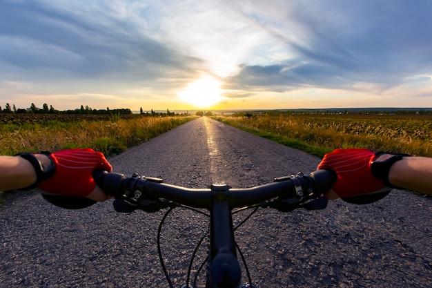 Handen op het stuur rijden een fietser op de weg naar zonsondergang