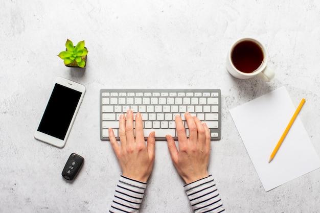 Handen op het toetsenbord, autosleutels, kopje koffie, blanco vel papier, een potlood en een kamer bloem op een concrete achtergrond.