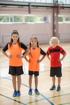 Handen op heupen. drie kinderen in lichte sportkleding staan met de handen op de heupen