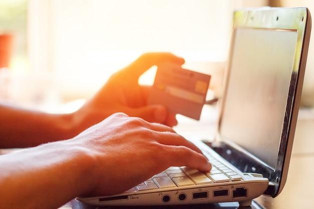 Handen op toetsenbord en telefoon met creditcard liggend op tafel, bedrijfsconcept