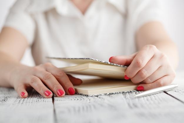 Handen open notebook op houten tafel