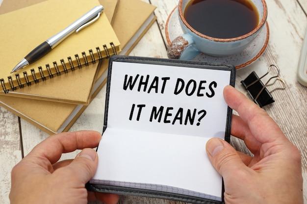 Handen openen een notitieboekje met de inscriptie wat betekent het op de achtergrond van het bureau