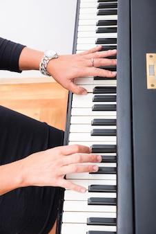 Handen os een klassieke musicusvrouw die op piano speelt.