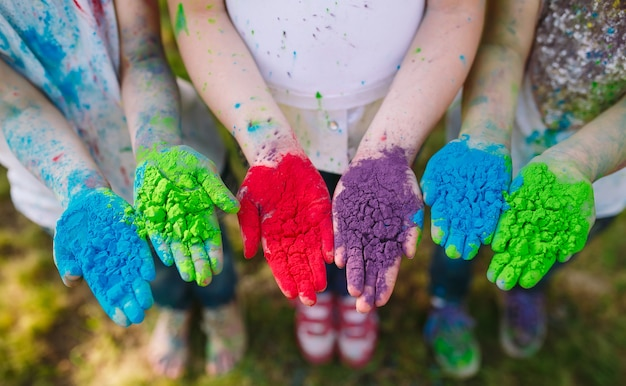 Handen / palmen van jonge mensen bedekt met paarse, gele, rode, blauwe holi festival kleuren geïsoleerd