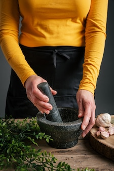 Handen pijnboompitten in een vijzel en stamper malen