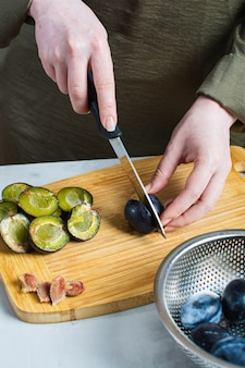 Handen pruimen snijden op een snijplank
