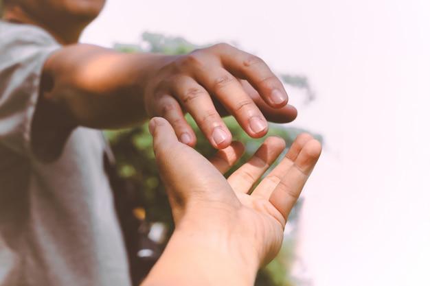 Handen reiken om elkaar te helpen.