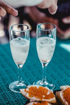 Handen ringen aanbrengend huwelijksglazen met sprankelende champagne