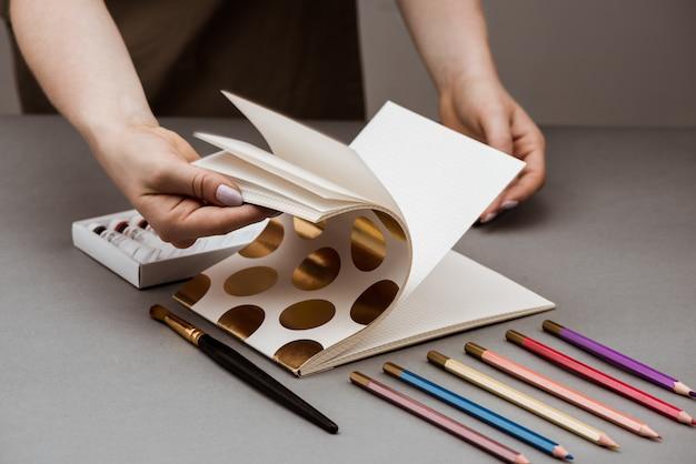 Handen schetsboek openen met olieverf en potloden op grijze tafel