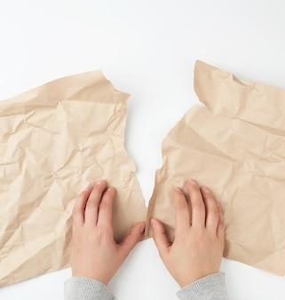 Handen scheuren een vel bruin ambachtelijk papier