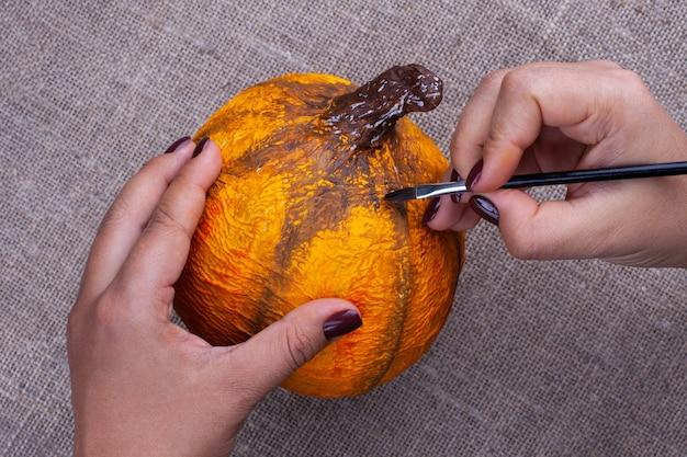 Handen schilderen met een penseel met gouache oranje kleuren ambachtelijke pompoen van papier-maché voor halloween