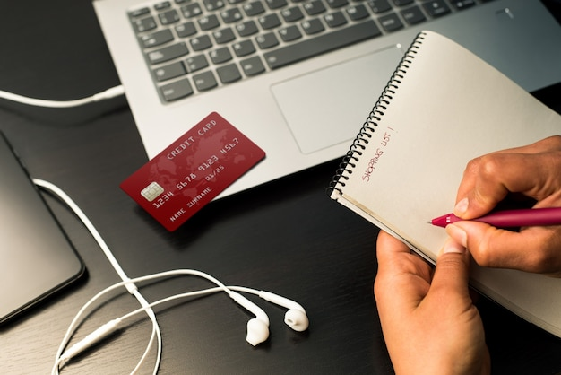 Handen schrijven boodschappenlijstje op de notebook klaar om online te winkelen