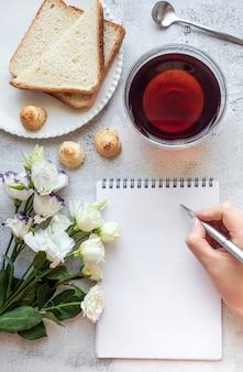 Handen schrijven op een kladblok ontbijt instelling kopie ruimte
