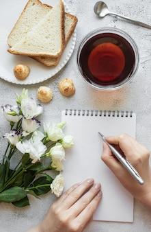 Handen schrijven op een notitieblok ontbijt instelling
